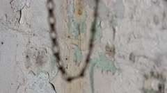A close up shot, rack focus from a chain swinging to a paint chipped wall. Stock Footage