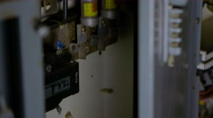 A tilt shot from bottom to top of electrical components mounted on a wall. Stock Footage