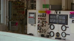 A pan shot left to right of a control board in an abandoned factory. Stock Footage