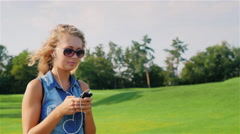 Young woman goes near a large golf course, listening to music on headphones in Arkistovideo
