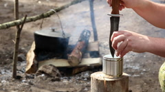 Person opens a can a big knife against a camp fire Stock Footage
