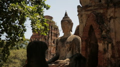 A Buddha statue in front of old ruins in Ayutthaya Historical Park, Thailand Stock Footage