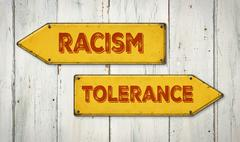 Direction signs on a wooden wall - Racism or Tolerance Stock Photos