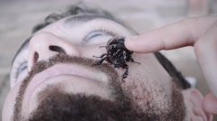Bug crawling on man face Stock Footage
