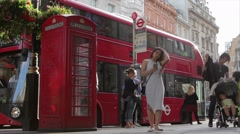 Passengers disembark red bus by London red phone booth Stock Footage