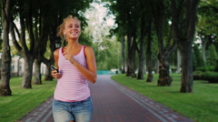 Young attractive woman runs in a beautiful well-kept park, listening to music Stock Footage