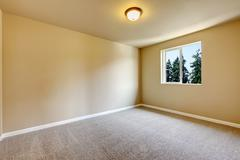 Bright empty room with one window, light gray carpet floor and beige walls. N Stock Photos