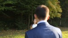 Bride and groom in love looking at each other at beautiful green forest Stock Footage