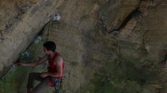 Rock climber cleaning holds covered in chalk in overhanging sandstone cliff Stock Footage