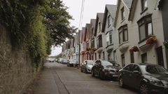 A dolly shot of a picturesque street with colored houses in Cobh, Ireland Stock Footage