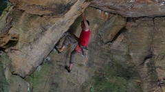 Rock climber trying hard move in overhanging sandstone cliff and falling Stock Footage