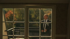 Handsome groom posing on the balcony of luxury hotel room apartments Stock Footage