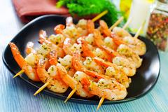 Boiled shrimps are beaded on sticks Stock Photos