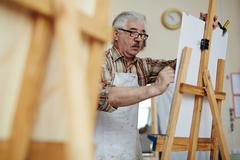 Male artist painting his picture at art studio Stock Photos