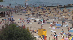 Pan right of busy sandy beach in summer hot day crowded people umbrella sunbed Stock Footage
