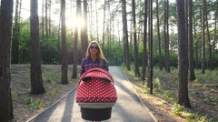Happy young mother with baby in buggy walking in park Stock Footage