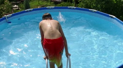 Weekend. Swimming pool. Young boy jumping into water in a pool. Slow motion. HD Stock Footage