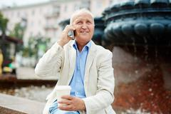 Senior man drinknig takeaway coffee and talking on the phone outdoors - stock photo
