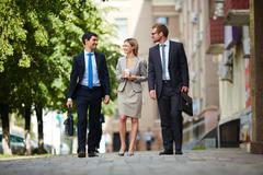 Successful young business people walking together outdoors Stock Photos