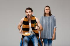 Man drinking beer, watching football, upset woman standing behind, crying Stock Photos