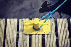 Yellow mooring bollard on wooden pier. Stock Photos