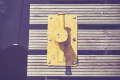 Yellow mooring bollard on wooden pier. - stock photo