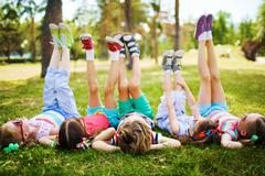 Children lying on the grass with their feet raised - stock photo