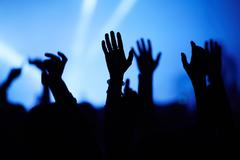 Silhouettes of people at concert with hands raised Stock Photos