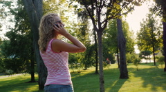 Young woman with long hair goes through the park, talking on the phone. The sun Stock Footage