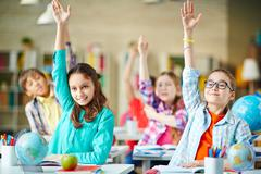 Intelligent group of school children raising their hands in to answer a question Stock Photos