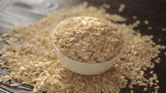 The oat flakes pouring in white plate on a wooden desk Stock Footage