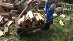 Male villager load chopped wood firewood and axe to rusty cart. 4K Stock Footage