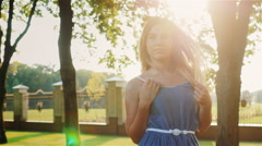 Portrait of attractive young girl with long hair. The sun is shining in her hair Stock Footage