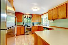 Bright kitchen with light brown cabinets, steel appliances and wooden counter Stock Photos