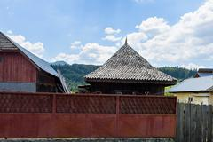 Photo of traditional wooden house with red fence and green forest in brasov m - stock photo