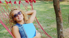Carefree young woman lying in a hammock and dream. The hand holding a book Stock Footage