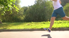 Runner in white tshirt running in the park. Crossing the frame. 4K steadicam Stock Footage
