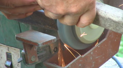 Worker man sharpen ax tool at industrial machine electrical spark iron equipment Stock Footage