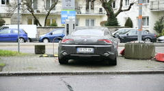 Rear view of Fisker Karma electric car charging in urban environment Stock Footage