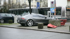 Side view of Fisker Karma electric car charging in urban environment Stock Footage