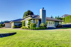 Nice curb appeal of modern blue siding house with well kept lawn and shrubs.  Stock Photos