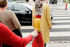 Woman at semaphore in Luxembourg waiting button - stock photo