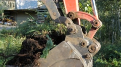 Shovel of an excavator take a scoop of dirt and vegetation. Stock Footage