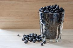 Blueberries in a glass with scattered berries. Vitamin charge for the day Stock Photos