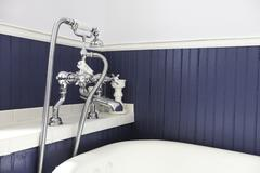 White tub with antique hardware and blue wood wall. Stock Photos