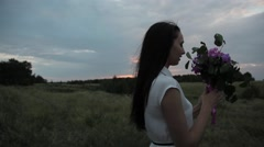 Girl with a bouquet in the field. Sunset Stock Footage