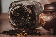 Asian teapot on stand and jar with scattering of tea Stock Photos