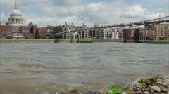 Water laps on the shore of the Thames with St Pauls Cathedral in background Stock Footage