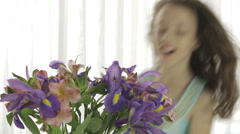 Beautiful girl enjoys bouquet of irises and alstroemeria Stock Footage