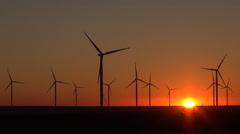 Timelapse wind turbine motion at sunset sun silhouette and windmill blades farm  Stock Footage